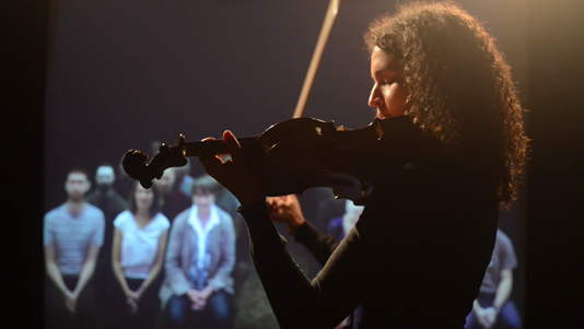 Woman playing violin to audience
